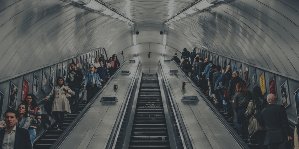 People riding escalators in subway station