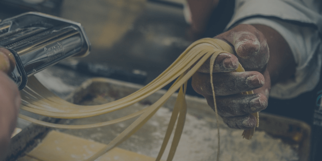 Pasta making machine with hand holding noodles