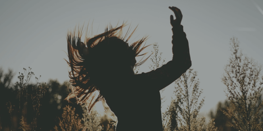 Silhouette of woman outdoors in sun with hand and hair in air