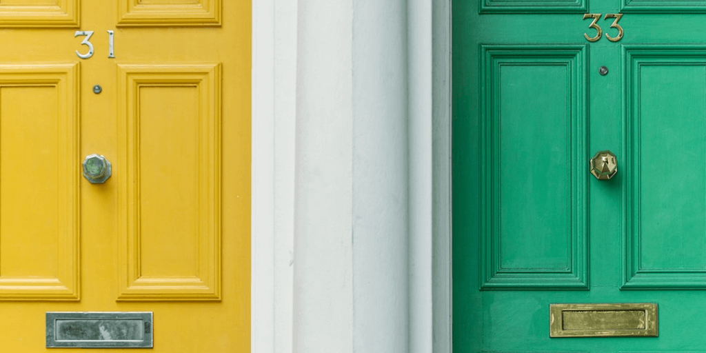 A yellow door with the number 31 next to a green door with the number 33