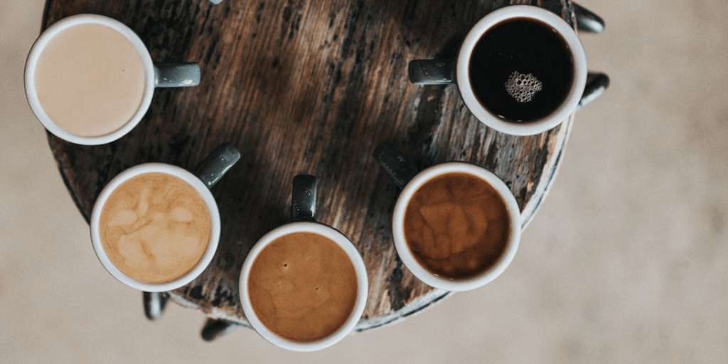 Five coffee cups arranged in semi-circle with varying levels of milk