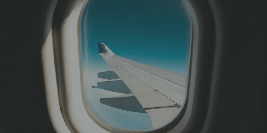 Looking through plane window at wing